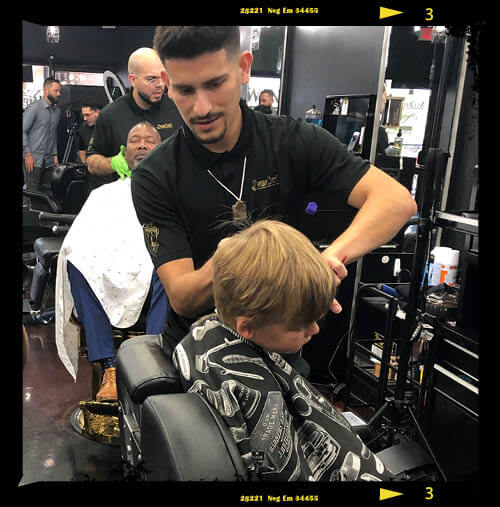 Photo of barber cutting kids hair at Twin Cutz